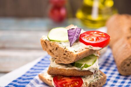 tomato slice: fresh sandwich with tomatoes and cucumber on wooden plate in studio Stock Photo