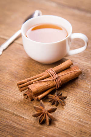 anis: fresh tea in white cup with cinnamon and anis in studio