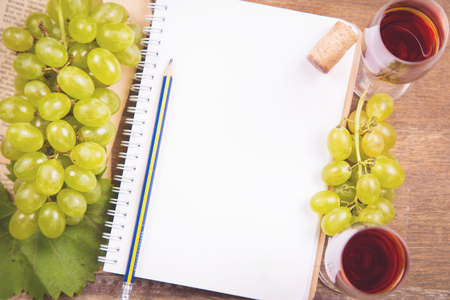 green grape with red wine,empty notebook,cork on wooden background