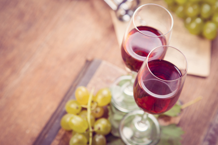 glass of red wine: green grape with red wine,cork on wooden background
