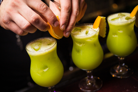 barmen: an alcoholic yellow cocktail is in beautiful glass, on the bar Stock Photo