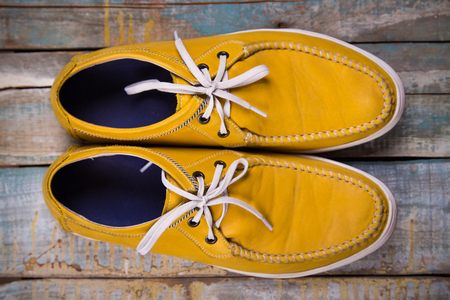 ropa de verano: pair of new leather yellow shoes on wooden background