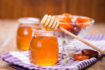 glass containers: fresh translucent flowers honey in glass containers with dry fruits Stock Photo