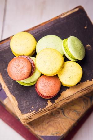 many colored: many colored macaroons on old book in studio