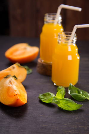 objec: fresh smoothie from persimmon with basil on wooden background