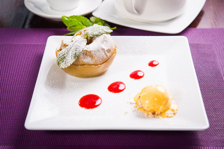 sherbet: baked apple with fresh mint,sherbet,and red sauce in white dish Stock Photo