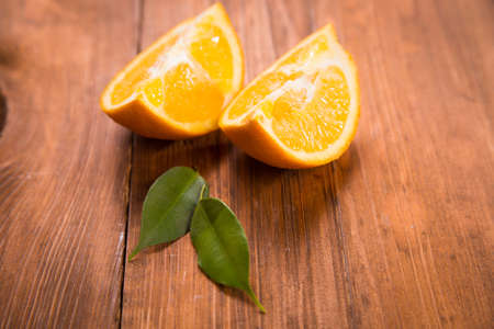 two pieces: two pieces of orange fruit with green leaf in studio