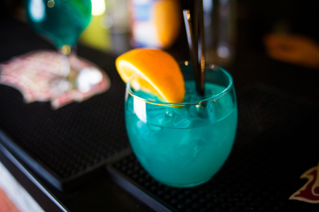 an alcoholic blue cocktail is in beautiful glass, in the restaurant
