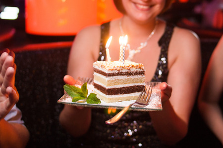 trumpery: cake with candles on plate in womans hand-birthday party Stock Photo