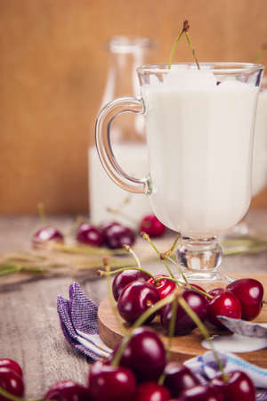 spica: yogurt in two glass with ripe cherry and spica on wooden background