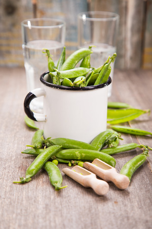 raw ripe fresh green peas in white cup with clear mineral water Stock Photo
