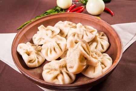 georgian: hot fresh georgian food,hinkali with parsley in restaurant Stock Photo