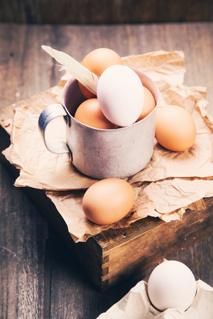 some fresh brown and white eggs in old cup in studio
