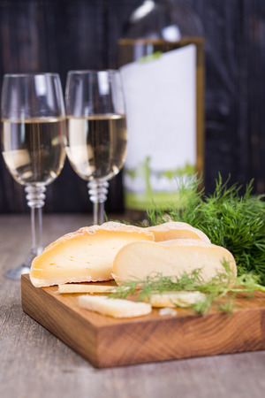 White wine in glasses and several types of cheese on wooden plate