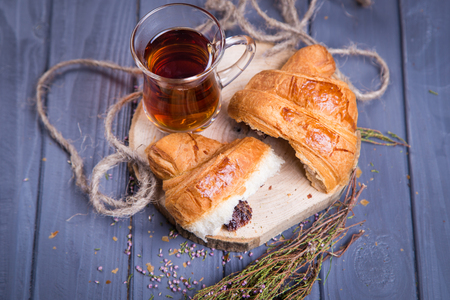 cup of tea with fresh croissant and dry violet flowers