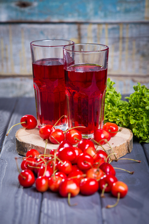 fresh cherries juice and many ripe cherrie on wooden background