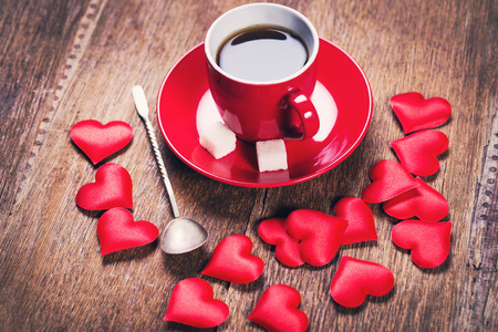 Morning breakfast for Valentines day. One cup of coffee and red hearts on old wooden background top view. Stock Photo