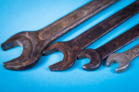 some old rough wrench on blue background in studio