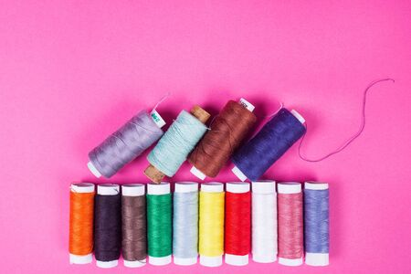 several spools of multicolored threads on a pink background in the studio