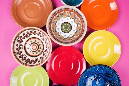 several new colored plates and bowls on a pink surface