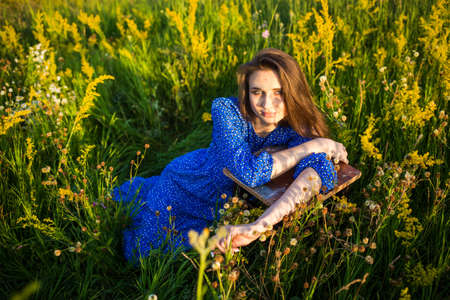 portrait of a beautiful young girl on chair, outdoors, in the field 免版税图像