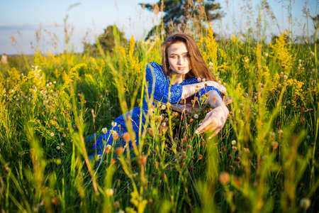 portrait of a beautiful young girl in blue dress, outdoors, in the field