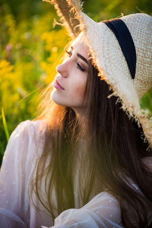 young beautiful european girl in the setting sun, on the field, in hat