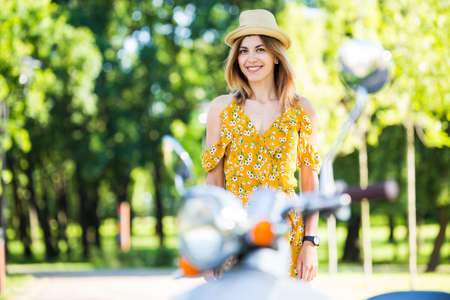 beautiful european girl in a yellow dress with a retro scooter in the morning park Archivio Fotografico