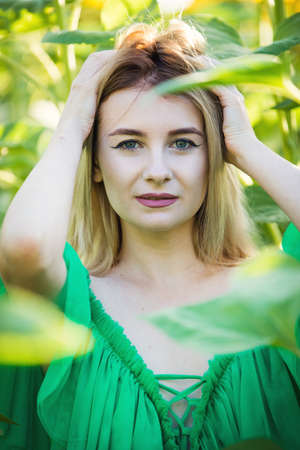 blond european girl in a green dress on nature with sunflowers
