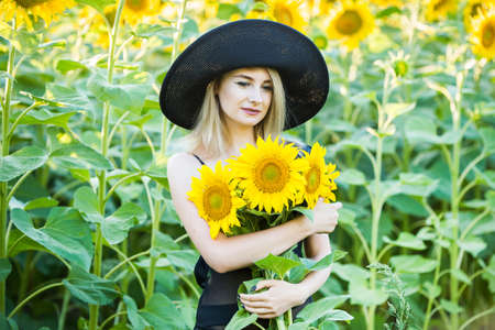 blond european girl in a black swimsuit and hat on nature with sunflowers