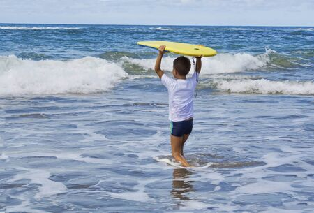Child entering .the water to play with the waves