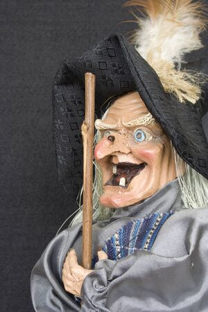 Close up of smiling witch with black background.