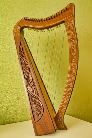 Carved harp on a white table with and green wall behind.