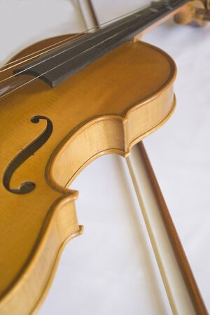Close up off violin and bow in a white background.
