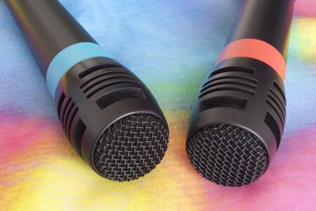 Karaoke microphones on top of a colorful material.