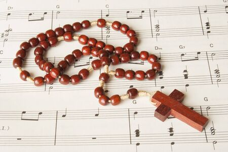 Wood rosary on a sheet of religious music.