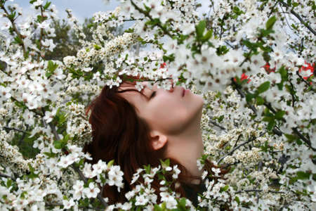 A beautiful girl enjoying the sunny weather in the middle of blooming cherry tree photo