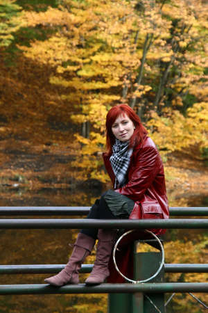 beautiful young woman with red hair, dressed in red jacket and red boots, relax in autumn park photo