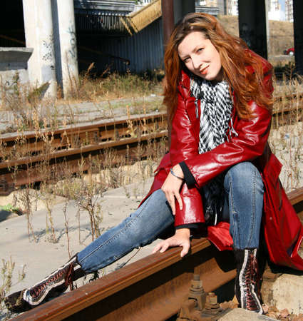 beautiful woman dressed in red jacket sit on railroad photo