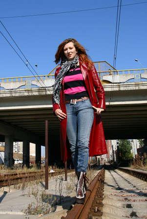 beautiful woman dressed in red jacket walking on railroad photo