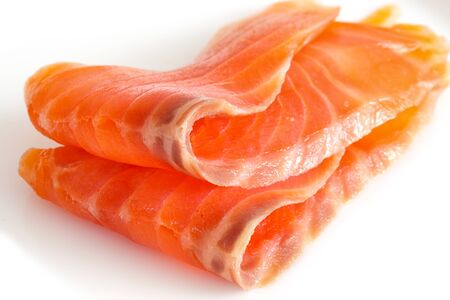 two slices of salmon on a white. Close up