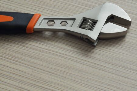 turning table: adjustable wrench closeup on wooden background. Extreme close up