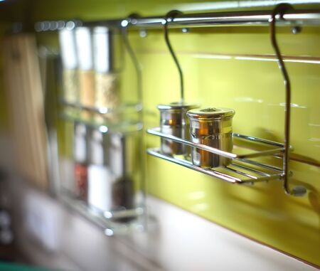 kitchen utensil: Salt Cellar and other spices in the kitchen railings. Shallow depth of field