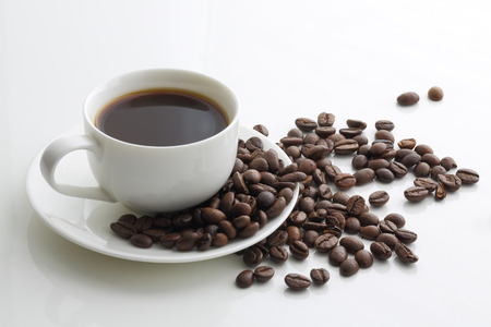 colombian food: White cup of coffee and coffee beans on a white background