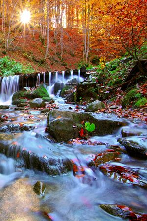 autumn landscape: Beautiful waterfall in forest at sunset. Autumn landscape, fallen leaves, water flow.
