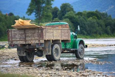 wade: old truck transports cargo wade across the river. Old dirty truck