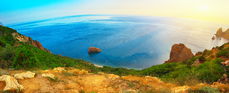 over the edge: Dramatic sunset at cape fiolent with rocks and grass at foreground. Panoramic view. Crimea Stock Photo