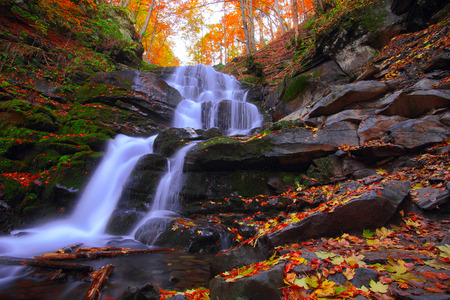 Beautiful waterfall in forest at sunset. Autumn landscape, fallen leaves, water flow.