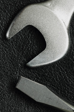 wrench spanner tool and screwdriver on black leather background