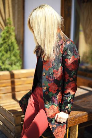 young beautiful stylish woman posing on street in floral printed coat, autumn fashion trend, smiling, happy